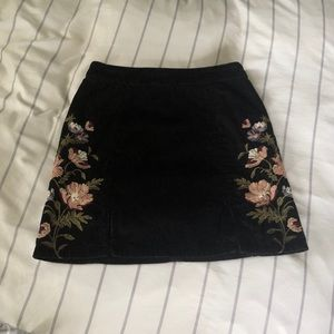 black corduroy skirt with floral detailing
